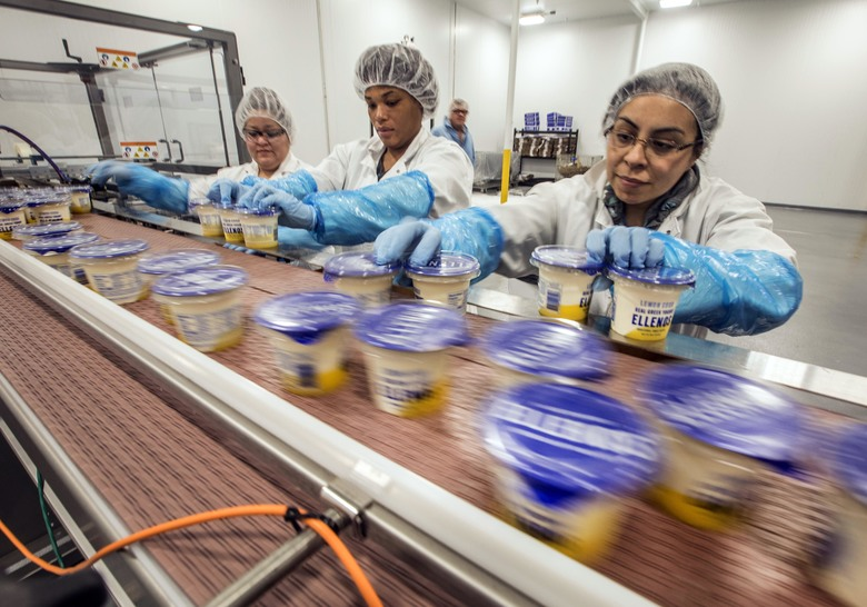 Ellenos employees — from left, Sandra Platero, LaQueena Saddler and Gabbi Garcia — grab yogurt containers coming down the line.  (Steve Ringman/The Seattle Times)