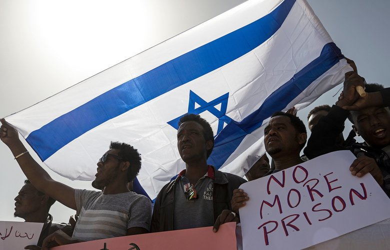 Asylum seekers march Feb. 22 during a protest outside Israeli Prison Saharonim, in the Negev desert, southern Israel. (Tsafrir Abayov / The Associated Press)