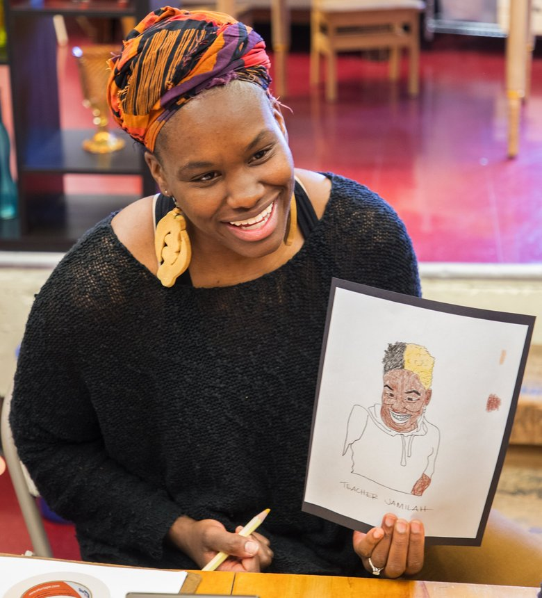 Jamilah Johnson, a teacher at The Pike Market Child Care and Preschool, demonstrates how to draw a self-portrait. The project is to teach kids about naming all of their different skin tones as a way to instill pride and confidence. The art exercise was done on March 27, 2018.  205744 (Mike Siegel / The Seattle Times)