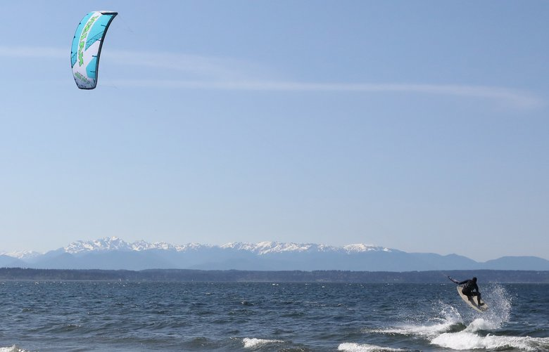 On Monday, April 23, Kite boarder Erik Sandstorm (cq) heads out across puget sound near Golden Gardens park, with the Olympic Mountains as a backdrop.  LO LO 206059
