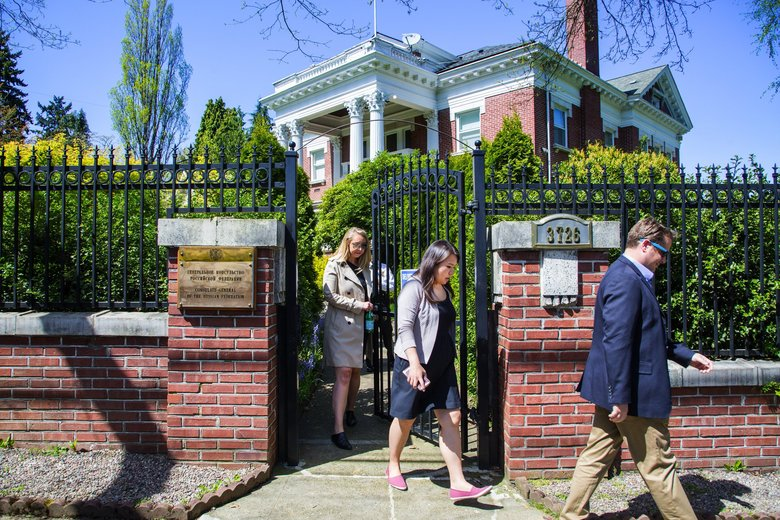 Officials with the U.S. Department of State walk out the front gate of the former Russian Consulate residence in Seattle. (Mike Siegel / The Seattle Times)
