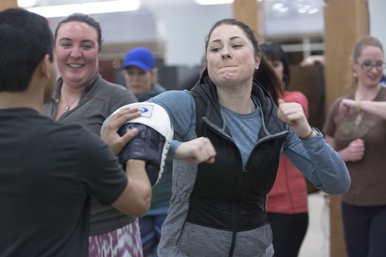 Marena Seidel, right, works on a self-defense move during a class taught by Fighting Chance Seattle at the RealSelf offices in Seattle. (Jason Redmond/Special to The Seattle Times)