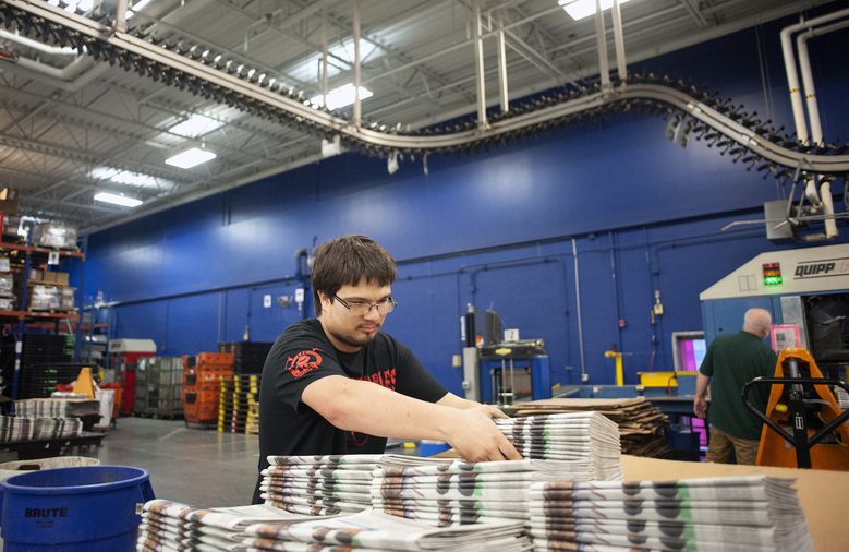 In this April 11, 2018, photo, production handler Joshuwa Conniff stacks newspapers onto a cart at the Janesville Gazette Printing & Distribution plant in Janesville, Wis. Newspaper publishers across the U.S. already strapped by years of declining revenue say they're dealing with an existential threat: Recently imposed tariffs on Canadian newsprint driving up their business costs. (Angela Major/The Janesville Gazette via AP)