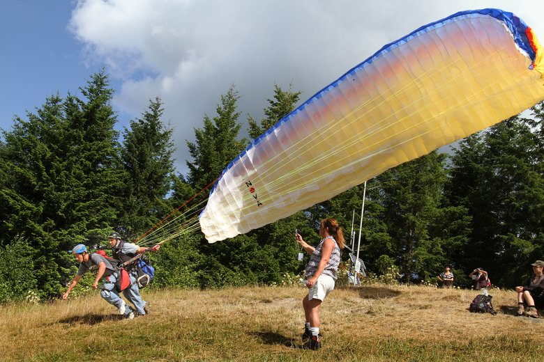 Novices try out paragliding at Poo Poo Point at Tiger Mountain. A shuttle service launched last summer to popular trailheads, including Poo Poo Point, will start again on April 21. It will serve more destinations this year. (Steve Ringman / The Seattle Times)