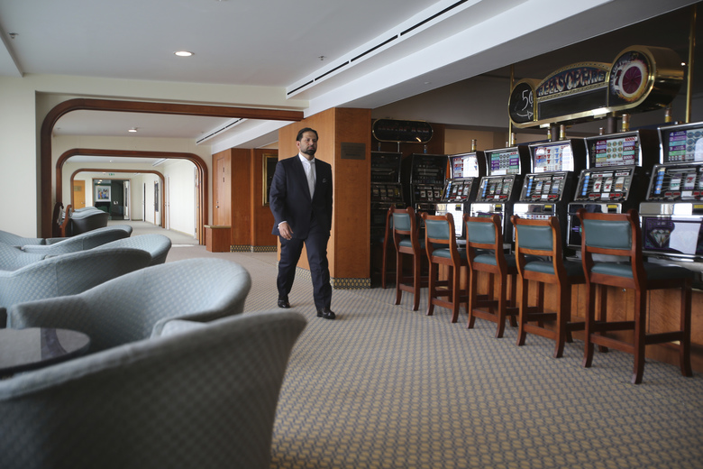 Hamza Mustafa, the CEO of Dubai's Ports, Customs and Free Zone Corp.'s investment arm, passes slot machines that will remain turned off as gambling is illegal, aboard the Queen Elizabeth 2, moored off the Mideast city-state of Dubai, United Arab Emirates, Tuesday, April 17, 2018. Britain's famed luxury cruise ship finally will have a soft opening Wednesday as a floating luxury hotel nearly a decade after arriving here following her last ocean voyage. (AP Photo/Kamran Jebreili)