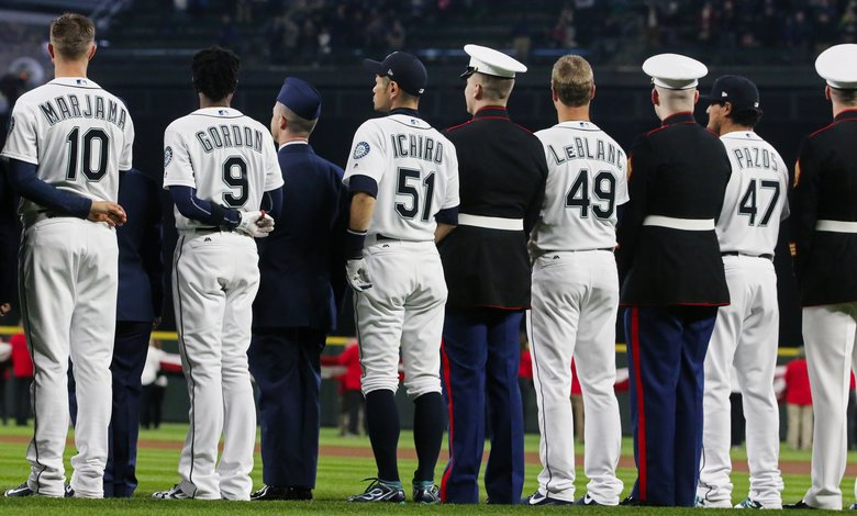 Mariners stand with members of the military services before the game against Oakland at Safeco Field. (Ken Lambert/The Seattle Times)