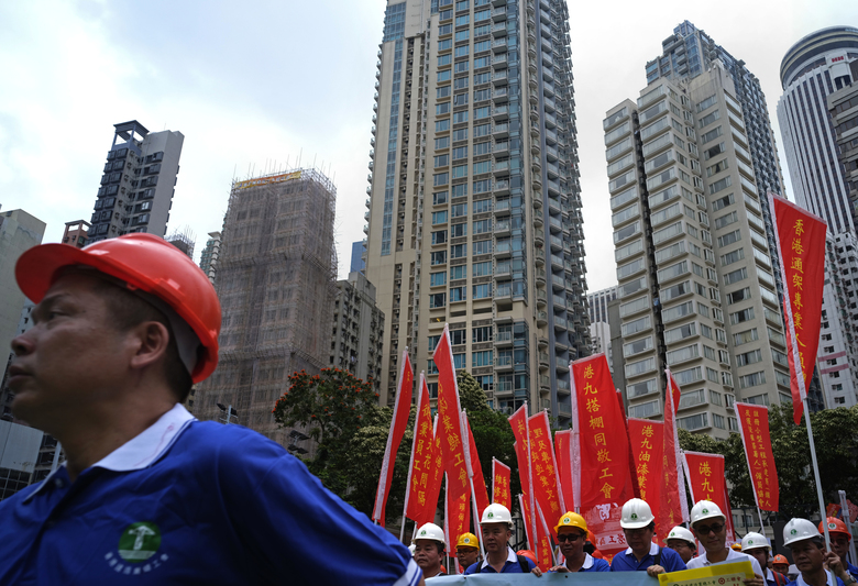 Workers wear safety hats and hold banners during a march to mark May Day in Hong Kong Tuesday, May 1, 2018. Hundreds of Hong Kong workers from various labor unions staged a rally to demand better workers' rights and call for standard working hours. (AP Photo/Vincent Yu)