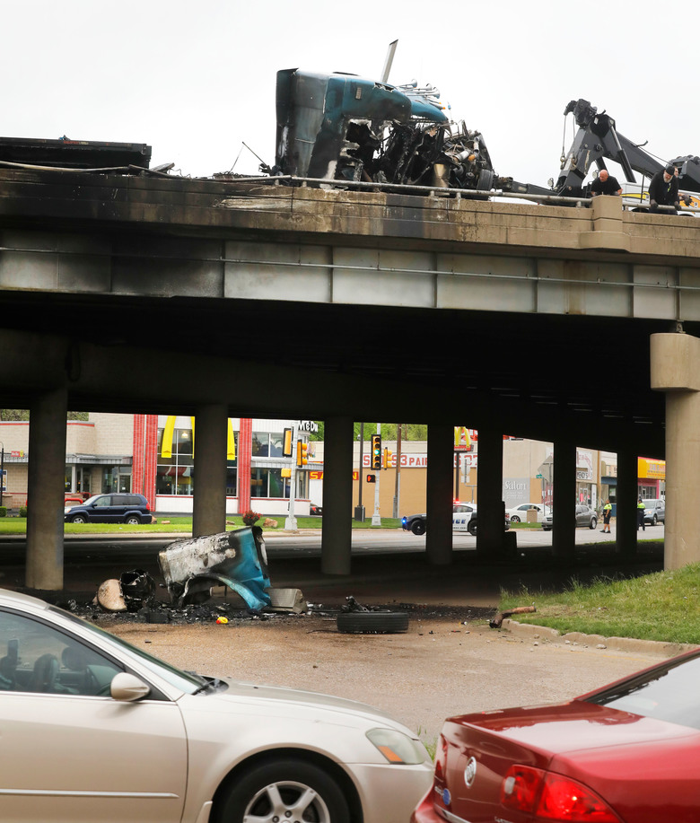 The cab of the 18-wheeler that exploded is left damaged after an accident at Interstate 30  in Dallas early Friday, April 6, 2018.    The cab is dangling from an overpass and the driver is dead after a fiery collision involving several vehicles on the interstate near downtown Dallas. At least three other vehicles were involved in the wreck Friday morning.  The tractor-trailer burst into flames and the truck driver later died at a hospital.   (David Woo/The Dallas Morning News via AP)