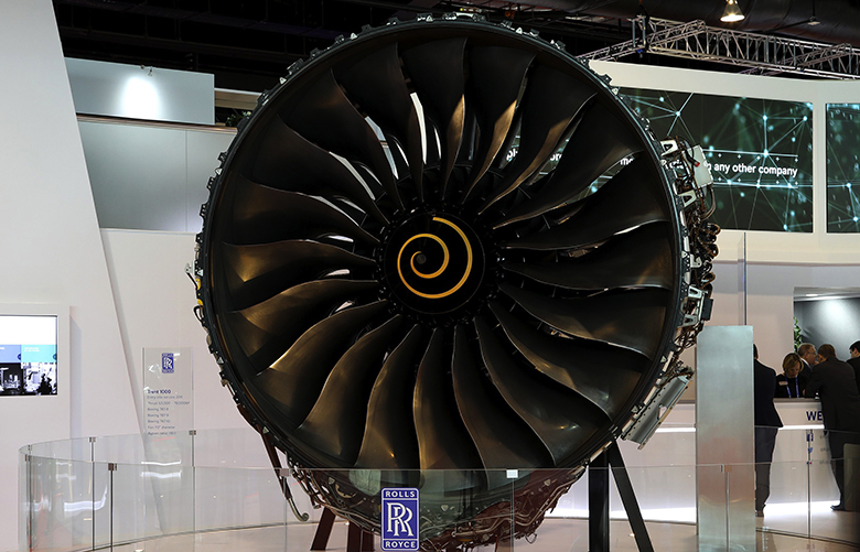 An attendee walks past a Rolls-Royce Holdings Plc Trent 1000 aircraft engine on display at the Singapore Airshow in Singapore, on Wednesday, Feb. 7, 2018. The air show runs through Feb. 11. Photographer: SeongJoon Cho/Bloomberg