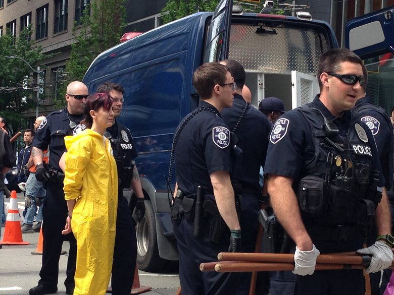 A haz mat suited demonstrator is arrested on Monday. (Lynda Mapes / The Seattle Times)