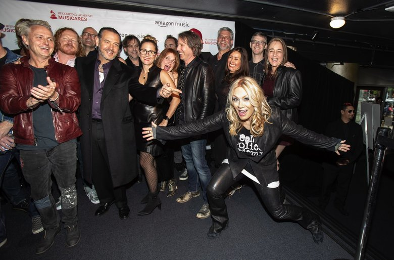 Nancy Wilson arrives just in time to join the group shot of performers at last night's Concert for Recovery at the Showbox. (Dean Rutz / The Seattle Times)