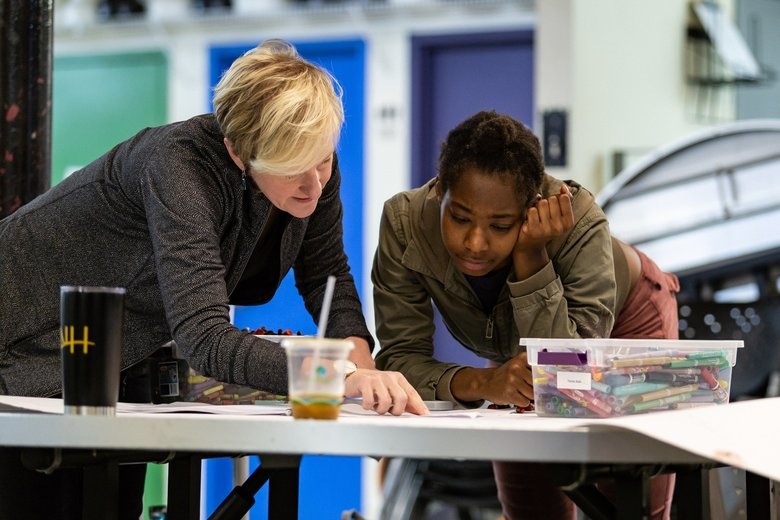 "Composer Alexandra Gardner, left, and Kaknnyy'GaDoughn (also known as CeeCee) look over the score for ""Stay Elevated"" at the New Horizons youth shelter in Belltown. (James Holt / Seattle Symphony)"