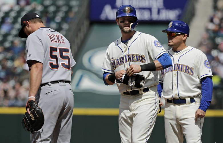 Seattle Mariners' Mitch Haniger, center, stands on first base next to Detroit Tigers first baseman John Hicks (55) and first base coach Chris Prieto, right, after hitting a single to break up a no-hitter in the seventh inning of a baseball game against the Detroit Tigers, Sunday, May 20, 2018, in Seattle. (AP Photo/Ted S. Warren) WATW114 WATW114