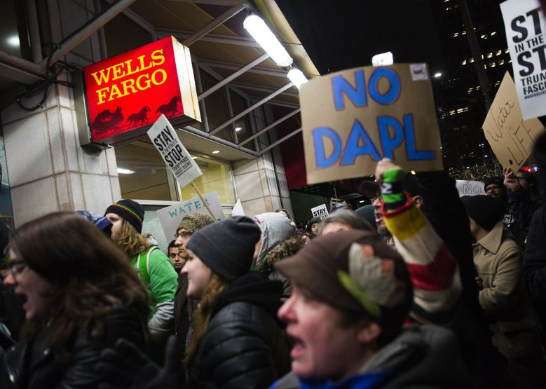 Dakota Access Pipeline protesters chant outside of the Wells Fargo Bank  at Westlake Center  in January 2017. The city of Seattle has renewed its contract with Wells Fargo, after it could get no other takers for its banking business. (Lindsey Wasson / The Seattle Times)