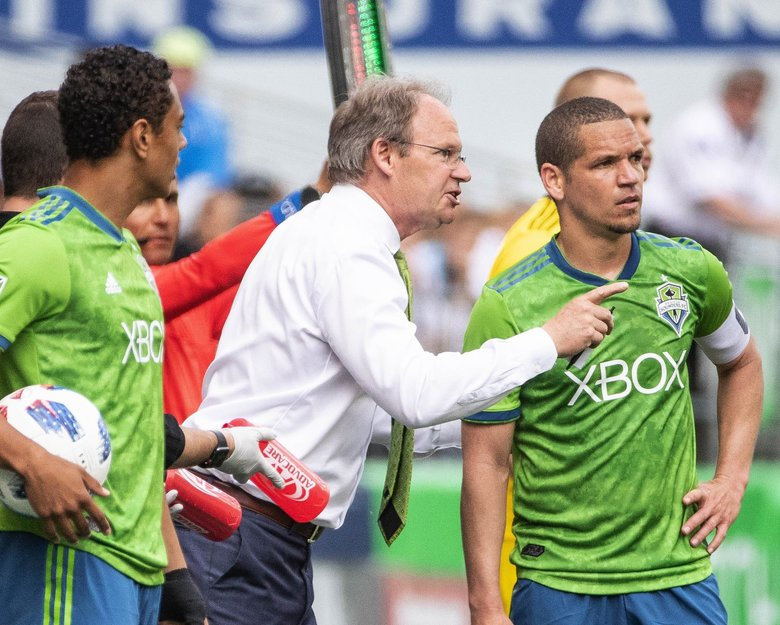 Whether he's interrupting his coach in a postgame talk to players or taking sideline instruction from him to relay to others, midfielder Osvaldo Alonso and Sounders coach Brian Schmetzer have a longstanding relationship of mutual reliance. (Dean Rutz / The Seattle Times)