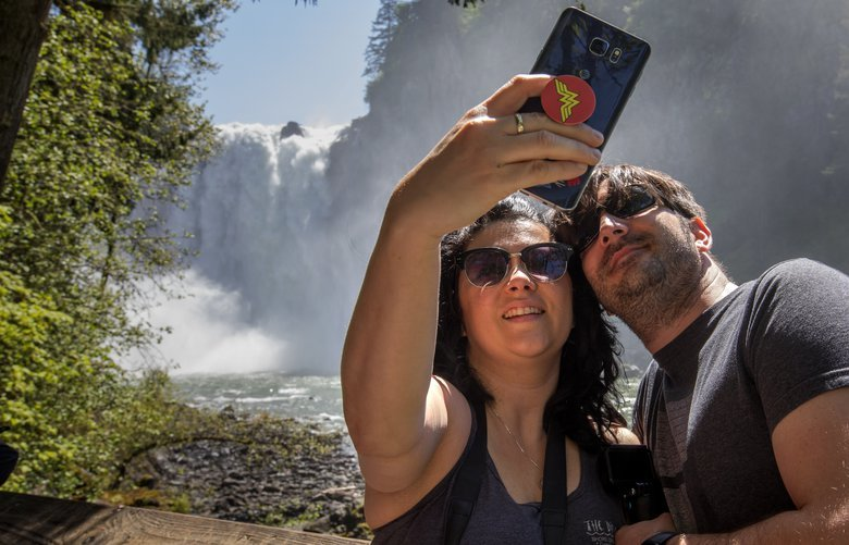 Amber Lane takes a selfie with Jesse Larrabee at the bottom of Snoqualmie Falls Monday, May 14, 2018.  The two are in the area on vacation from their home in Indianapolis, Indiana.  The 268-foot waterfall is one of Washington state's most popular scenic attractions.