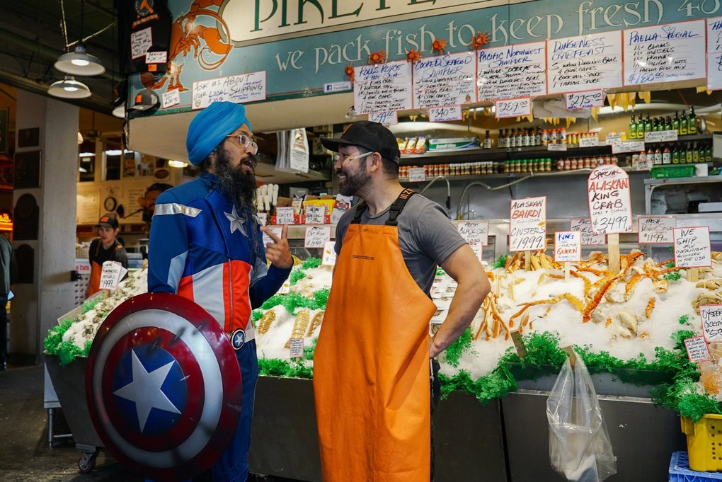 Vishavjit Singh speaks with Taho Kakutani, a fishmonger at Pike Place Fish Company. Singh uses his costume to open conversations with others about being Sikh in America. (Corinne Chin / The Seattle Times)