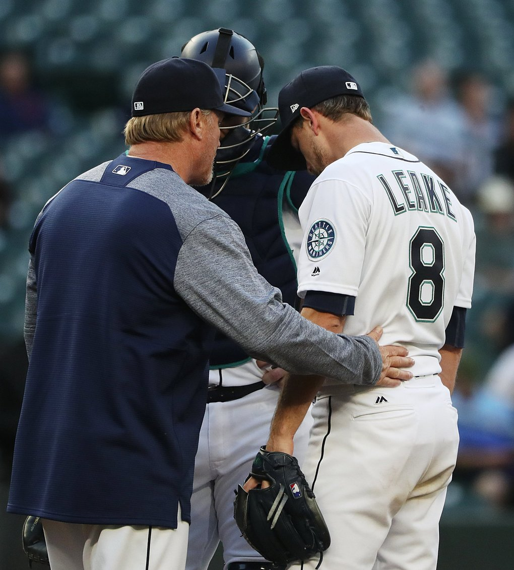 Mariners starting pitcher Mike Leake (8) gets an encouraging pat from pitching coach Mel Stottlemyre during a tough second inning where Texas scored three runs. (Ken Lambert / The Seattle Times)