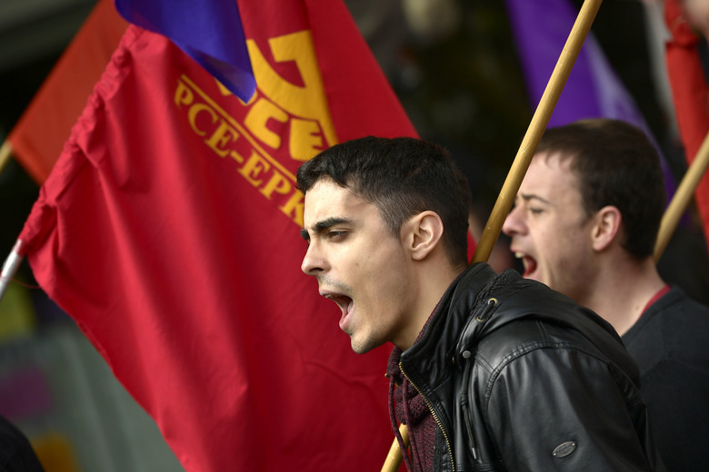 Demonstrators shout slogans during a May Day rally in Pamplona, northern Spain, Tuesday, May 1, 2018. More than 70 cities across Spain are holding May Day marches calling for equal gender rights, higher salaries and pensions now that the country's economy is back in the path for growth. (AP Photo/Alvaro Barrientos)