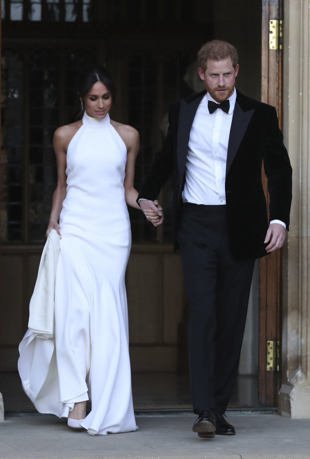 The newly married Duke and Duchess of Sussex, Meghan Markle and Prince Harry, leave Windsor Castle after their wedding in Windsor near London Saturday, May 19, 2018 to attend an evening reception at Frogmore House, hosted by the Prince of Wales.  (Steve Parsons/pool photo via AP)