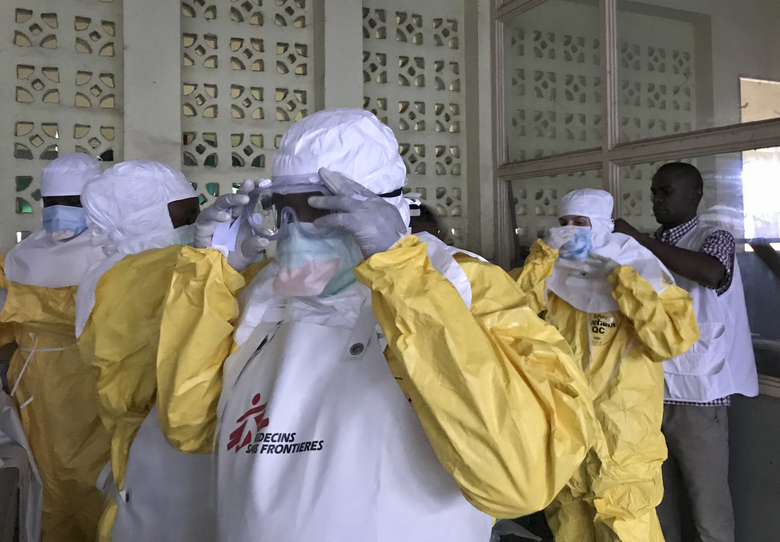 In this photo taken Sunday, May 20, 2018, a team from Medecins Sans Frontieres (Doctors Without Borders) dons protective clothing and equipment as they prepare to treat Ebola patients in an isolation ward of Mbandaka hospital in Congo. Congo's health ministry announced Tuesday, May 22, 2018 six new confirmed cases of the Ebola virus and two new suspected cases while a vaccination effort enters its second day. (Louise Annaud/Medecins Sans Frontieres via AP)