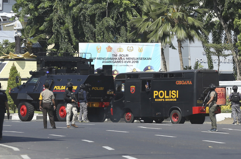 Police vehicles are parked outside local police headquarters following an attack in Surabaya, East Java, Indonesia, Monday, May 14, 2018. The police headquarters in Indonesia's second largest city was attacked Monday by suspected militants who detonated explosives from a motorcycle, a day after suicide bombings at three churches in the city by members of one family killed a number of people. (AP Photo/Achmad Ibrahim)