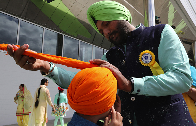 A Sikh father wraps his son's turban before entering the ShoWare Center in Kent for the Khalsa Day Celebration Saturday.  Thousands came to mark the day with sacred hymns, vegetarian food and a parade later in the afternoon.Ref to More Photos online.LO Saturday May 26, 2018