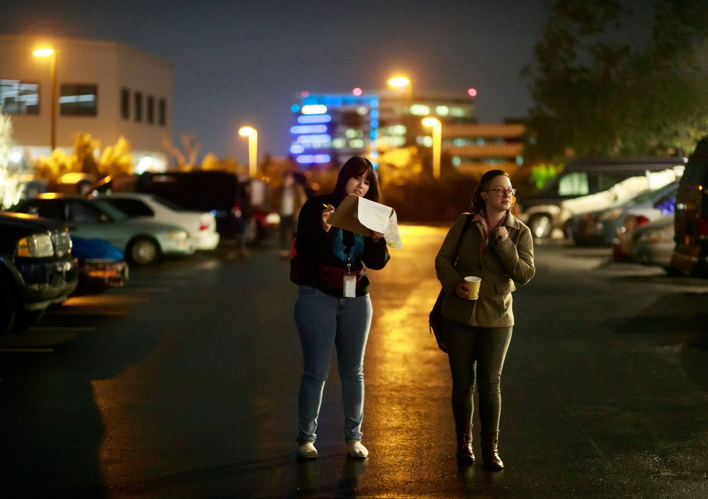 In San Diego's safe-lot program, case managers are on site for several hours every night. Here, Michelle Rios, program assistant for Jewish Family Service of San Diego, and Keely Kiczenski, case manager for Dreams for Change, check to see if the vehicles in the safe lot are registered to be there. This site has space for 60 vehicles.  (Erika Schultz/The Seattle Times)