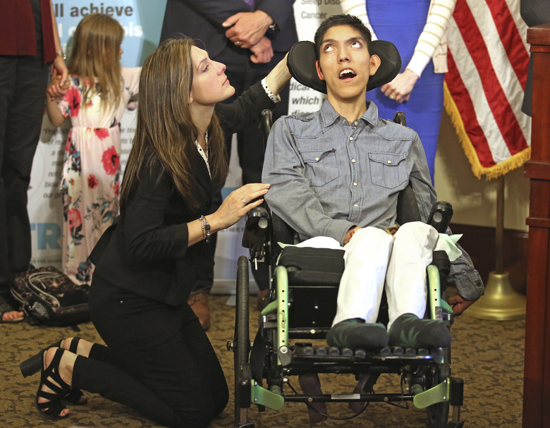 FILE – In this May 8, 2018, file photo, Desiree Hennessy attends to her adopted son Hestevan, who has cerebral palsy and suffers from chronic nerve pain, seizure disorder during a news conference at the Utah State Capitol, in Salt Lake City, as supporters of a medical-marijuana ballot initiative fend off opponents' increasing efforts to keep them off the ballot. Medical-marijuana supporters in Utah are pushing back in court against opponents trying to block them from the ballot by citing federal drug law. (AP Photo/Rick Bowmer, File)