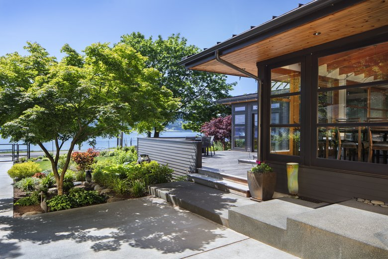 "Bob and Mary Carlson's Bainbridge Island home originally was a 1930s-era cabin. Architect Tom Kundig remodeled it in the early 1980s, and now architect Tom Kuniholm has done a major remodel that expands and updates ""many of those aesthetic cues,"" he says. Bob Grimm was the builder for the remodel (Bob Carlson did a lot of hands-on work himself, and Mary Carlson handled interior design).  (Steve Ringman/The Seattle Times)"