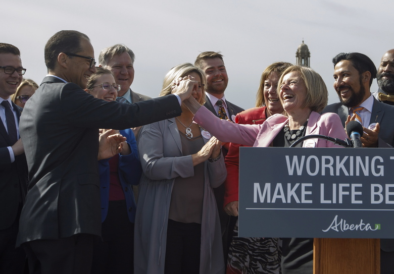 Alberta Premier Rachel Notley high fives Finance Minister Joe Ceci at a press conference to speak about the Kinder Morgan pipeline project, in Edmonton on Tuesday, May 29, 2018. The federal Liberal government announced Tuesday that it will spend $4.5 billion to buy Trans Mountain and all of Kinder Morgan Canada's core assets. (Jason Franson/The Canadian Press via AP)
