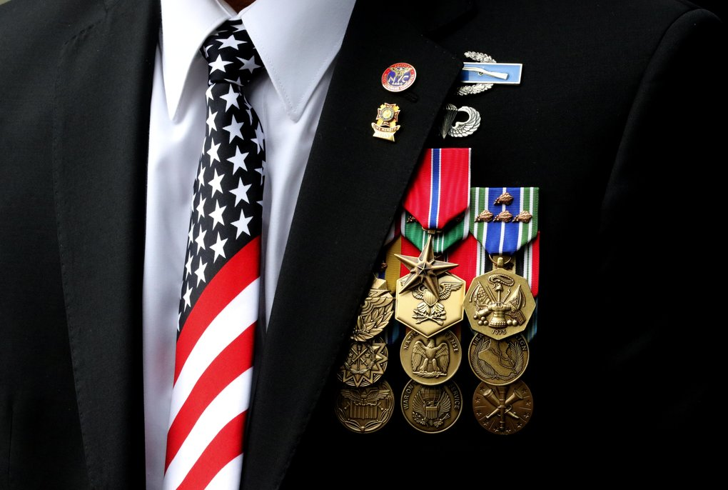 Nisei Veterans Committee Commander Walt Tanimoto wears a Stars & Stripes tie along with many medals, including the Bronze Star he was awarded. He provided a welcome to those who came to honor the Japanese Americans who served.  (Alan Berner/The Seattle Times)