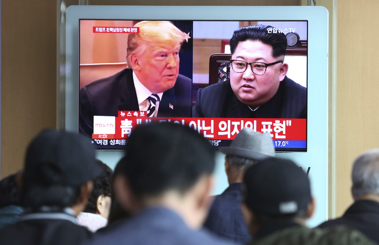 """People watch a TV screen showing file footage of U.S. President Donald Trump, left, and North Korean leader Kim Jong Un during a news program at the Seoul Railway Station in Seoul, South Korea, Sunday, May 13, 2018. North Korea said Saturday that it will dismantle its nuclear test site in less than two weeks, in a dramatic event that would set up leader Kim Jong Un's summit with President Donald Trump next month. Trump welcomed the """"gracious gesture."""" (AP Photo/Ahn Young-joon)"""