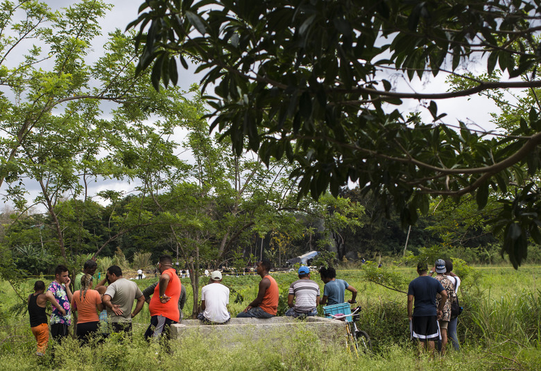 People look from far at the remains of a Boeing 737 that plummeted into a yuca field with more than 100 passengers on board, in Havana, Cuba, Friday, May 18, 2018. The Cuban airliner crashed just after takeoff from Havana's international airport. (AP Photo/Desmond Boylan)