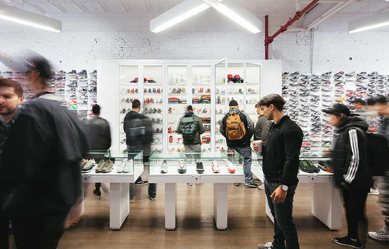 — PHOTO MOVED IN ADVANCE AND NOT FOR USE – ONLINE OR IN PRINT – BEFORE MAY 13, 2018. — Shoppers checking out the merchandise at Stadium Goods in New York, March 28, 2018. Some of the more expensive sneakers are encased in glass. (Mark Wickens/The New York Times)