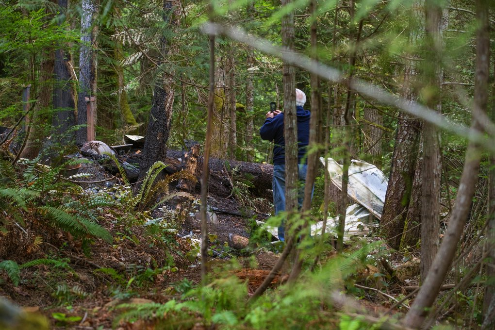 Meril Smith, a Jefferson County District 4 Fire Commissioner, surveys the rubble where five people were killed Sunday morning after an explosion and fire destroyed their cabin on this lot in the Brinnon area bordering Hood Canal.  (Mike Siegel / The Seattle Times)