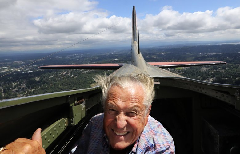 Fred Radke hangs on as he rises up through the hatch atop a World War II B-17 bomber flying over Seattle on Friday. The emergency hatch is removed for the flight to provide natural air conditioning inside the bomber and is over the radio operator's compartment. (Alan Berner / The Seattle Times)