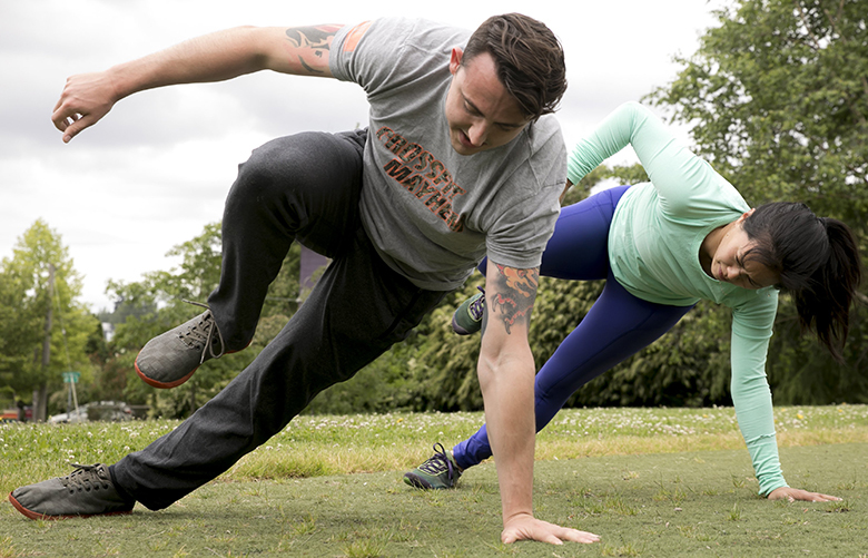 "Nicole Tsong learns how to do the ""Lizard Walk"" with trainer Kyle Long in a crawling and locomotion workout at Judkins Park in Seattle Tuesday May 29, 2018."