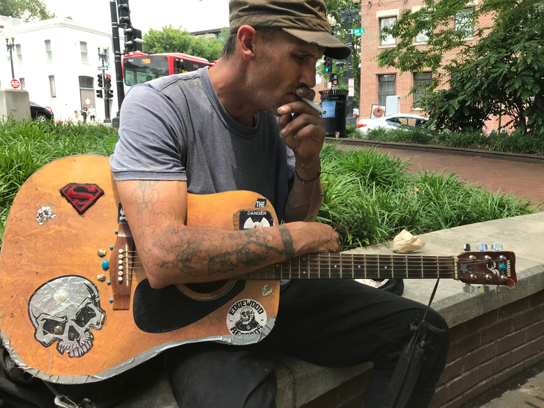 Pete Andersen, who is homeless, plays guitar in Francis Scott Key Park in Washington, D.C. Andersen says the park, has been a good place to spend his days.  (David Montero/TNS)