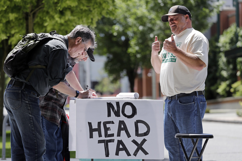 Gathering signatures May 24 in Seattle to put on the November ballot a referendum on Seattle's head tax. Mayor Jenny Durkan and a majority of the City Council announced Monday they now want it repealed. (Elaine Thompson / AP)
