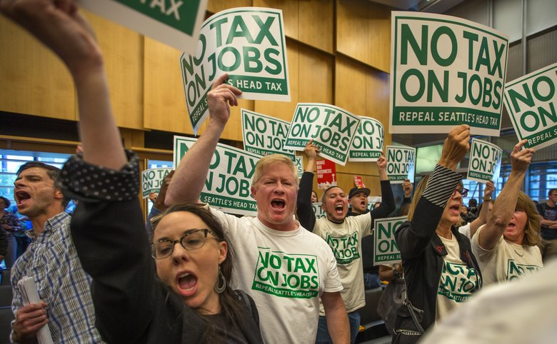 Anti-head-tax supporters shout their approval of the Seattle City Council's repeal during the voting process Tuesday at City Council Chambers. (Mike Siegel / The Seattle Times)