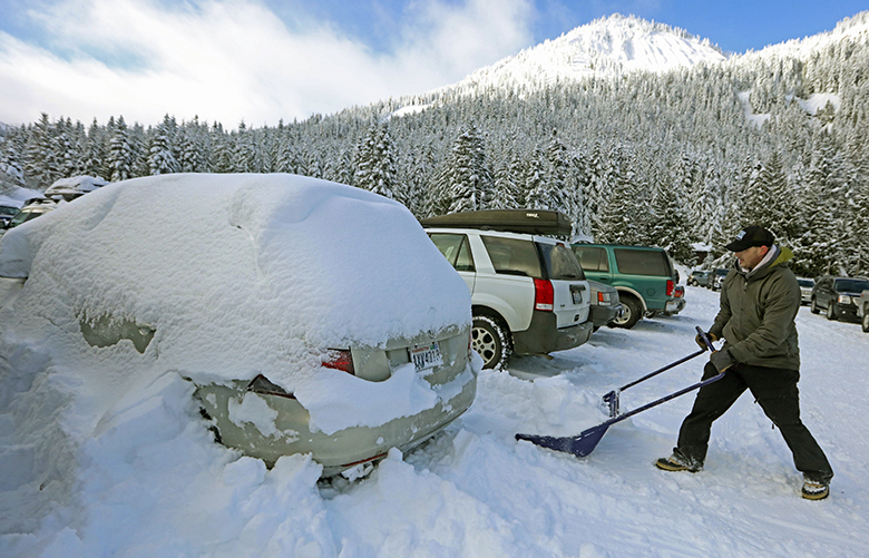 Thursday, December 24, 2015.   A skier digs out his car after a week in the Crystal Mountain parking lot. Storm water runoff from the parking lots at Crystal has been the focus of legal action.