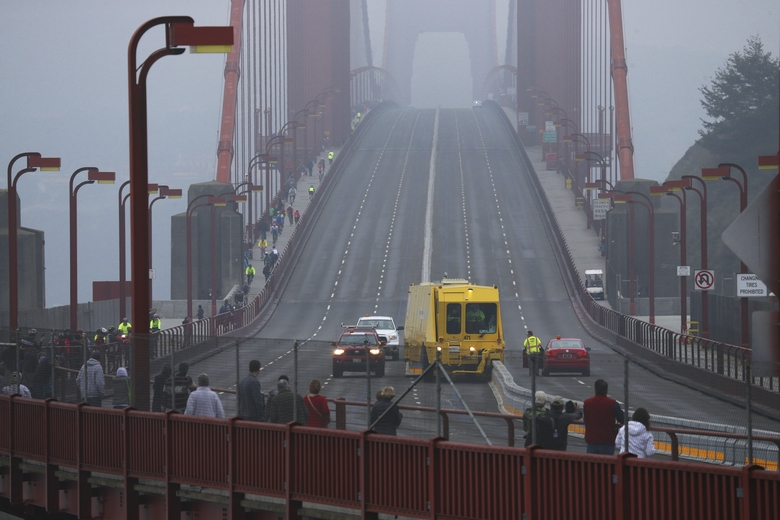 Pedestrians watch a then-new Road Zipper system in action on the Golden Gate Bridge in 2015. The zipper helps prevent crossover accidents and it can be moved to allow different lane configurations depending on traffic patterns.  (JIM WILSON/NYT)