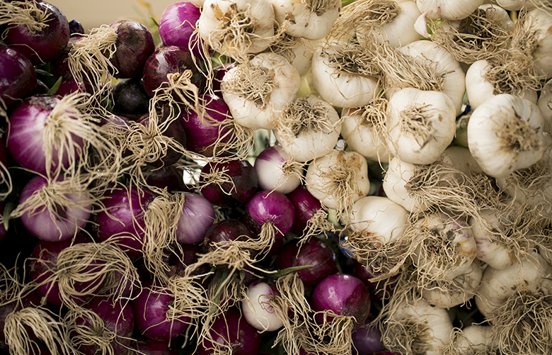 Onions and garlic on display at the Alvarez Organic Farms stand at the West Seattle Farmers Market Sunday June 3, 2018.