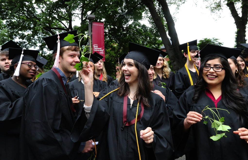 Adde Breier, center, waves a sprig of ivy to her mom in the audience Friday. Breier is receiving a bachelor<br/>'s degree in music therapy.  (Alan Berner/The Seattle Times)
