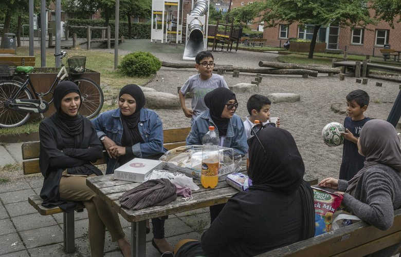 Rokhaia Nassan, center, with her back turned, in Mjolnerparken, a housing project that is classified as a ghetto by the Danish government, in Copenhagen, June 18, 2018. The Danes, who have struggled to integrate non-Western families, are getting tough: From age 1, immigrant children will receive mandatory instruction in ?Danish culture.? Nassan resents the new program. (Mauricio Lima/The New York Times) XNYT XNYT