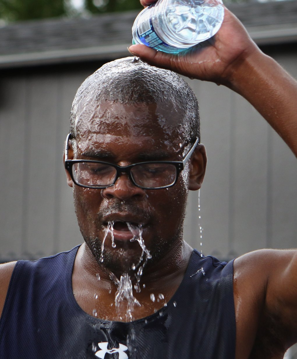 After placing second in the Special Olympics 5000M Run, Division M02, at the University of Washington, Andrew Peterson from Indiana douses himself in water Monday, July 2, 2018.  (Ellen M. Banner / The Seattle Times)