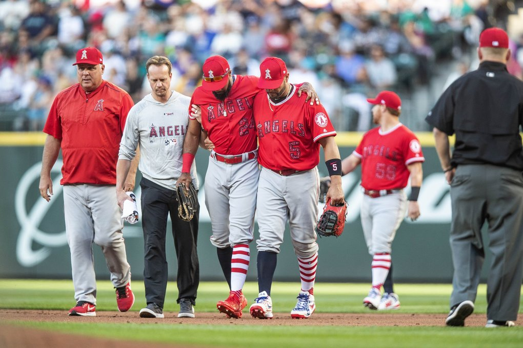 Angels right fielder Chris Young is helped off the field by Albert Pujols and a trainer after suffering a fielding injury in the 1st inning.  (Dean Rutz / The Seattle Times)
