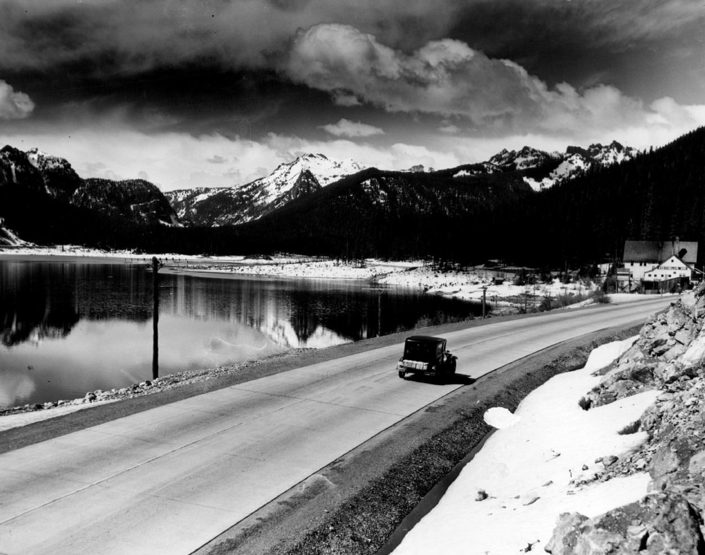 This July 12, 1936, view shows the snow-clad Cascades from a point on the Sunset Highway east of Snoqualmie Pass.  Adjoining the highway is the mirror-like Keechelus Lake, one of the reservoirs for the Yakima River irrigation systems. (Seattle Times archives)