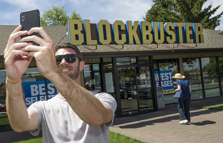 Scott Thornton takes a selfie in front of the Bend, Ore., Blockbuster on Friday, July 13, 2018. The Bend store is the last remaining Blockbuster in operation in the United States after two stores in Alaska closed earlier this week. (Ryan Brennecke /The Bulletin via AP) ORBEN201 ORBEN201